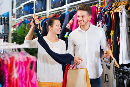 sleeveless hoodie: Smiling happy couple examining various sports clothes in sports store