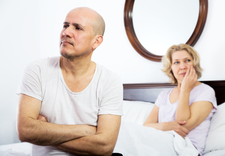scandals: Mature couple getting through scandals and blamings in bedroom Stock Photo