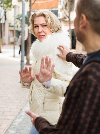 senior woman asking man not to bother her outdoor