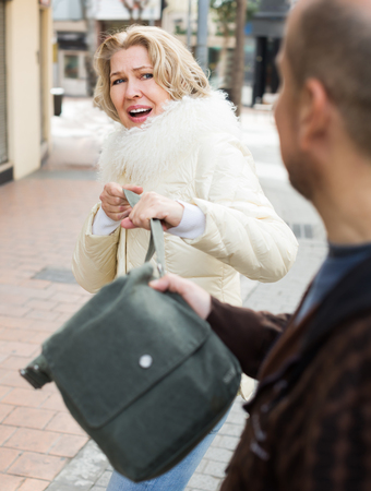 Portrait of frightened elderly woman and robber stealing bag