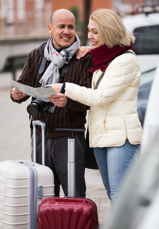 Cheerful elderly couple with luggage standing at street and checking direction Stock Photo