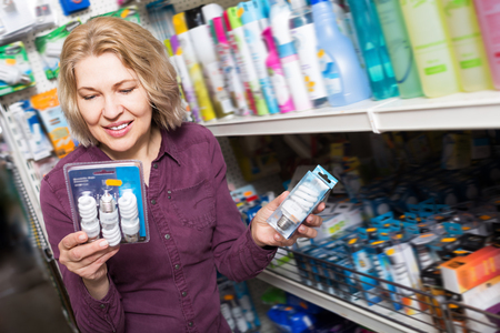 homeware: Mature woman buys light bulbs at the hardware store department