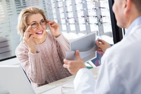 Senior male optician offering glasses frames to elderly woman