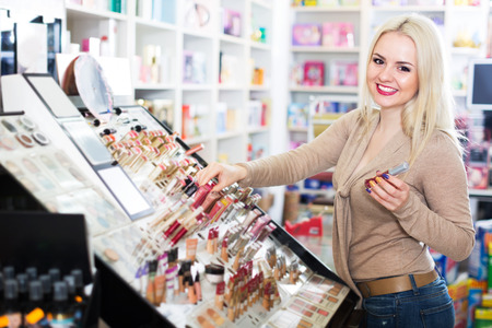 Happy blond woman choosing lip plumper on display and smiling