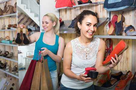 Two happy young female friends choosing fashion shoes in the shoes store Stock Photo
