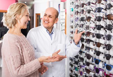 Professional spanish male optician consulting mature blonde customer near sunglasses display