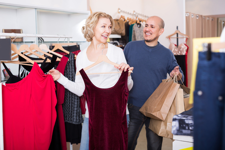 frock: Couple choosing new fancy dress in clothing store Stock Photo