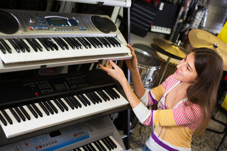 Happy girl selecting control keyboard for synthesiser in shop Stock Photo