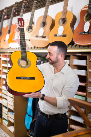 Cheerful male customer choosing acoustic guitar in music instruments shop