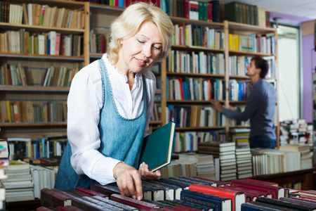 mature woman searching for new book on shelves in book store