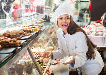caucasian shopgirl posing with delicious chocolate and confectionery Stock Photo