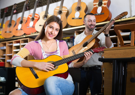 Cheerful young couple of musicians playing acoustic guitar in music instruments shop