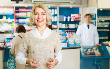 Positive mature female patient near counter in pharmacy drugstore