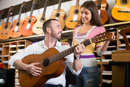 Portrait of smiling customers in music instruments shop