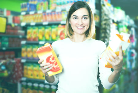 sorts: Smiling young girl searching for beverages in supermarket Stock Photo