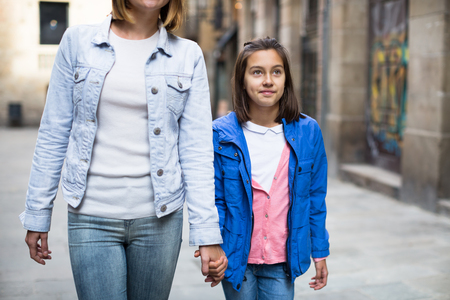 Young mother and daughter taking walk in city during the sightseeing tour Stock Photo