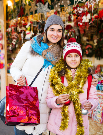 Portrait of positive little girl with mom buying decorations for Xmas. Focus on girl