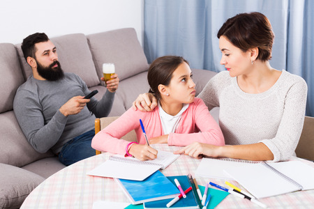 study group: Young mother explaining homework to her daughter at home
