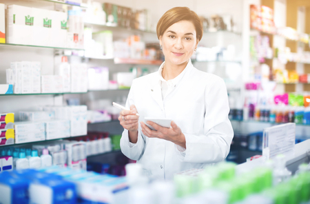 cures: Young diligent friendly female pharmacist noting assortment of drugs in pharmacy Stock Photo