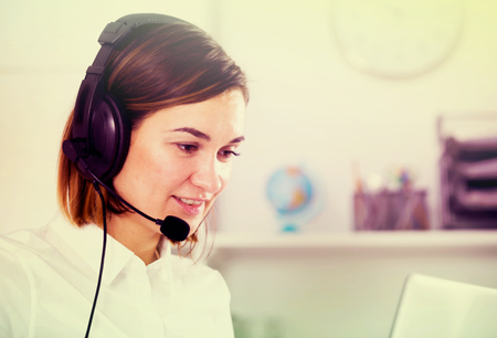 expertize: Smiling woman worker working effectively at call-centre