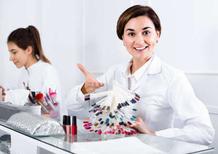 schemes: Satisfied female manicurist showing lacquer color schemes in nail salon Stock Photo