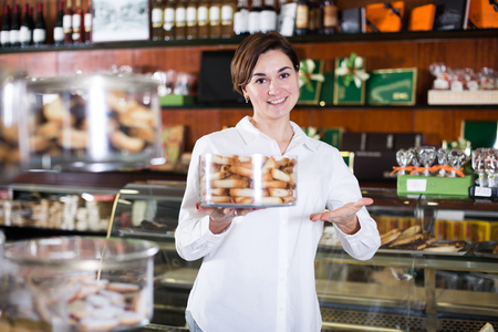 patisserie: Young female seller offering tray of sweet rolls in confectionery Stock Photo