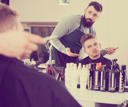 scandalous: Client looking displeased about his new haircut at hair salon Stock Photo