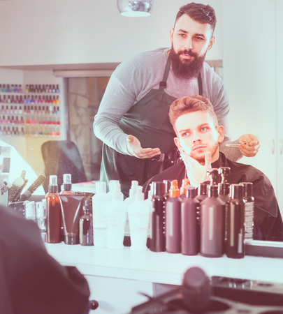 adult american client feeling discontent about his new haircut at hair salon