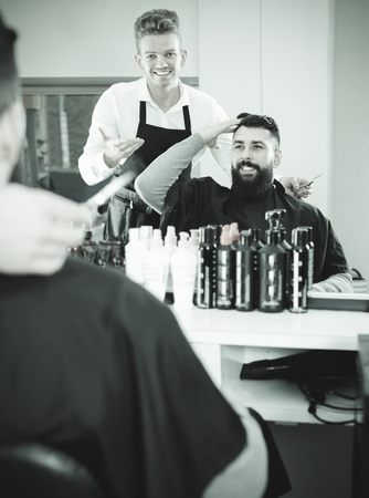 haircutter: Young smiling friendly client making specifications about haircut with hairdresser at salon