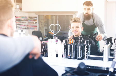 haircutting: Adult man hairdresser displaying result of work to client at hair salon