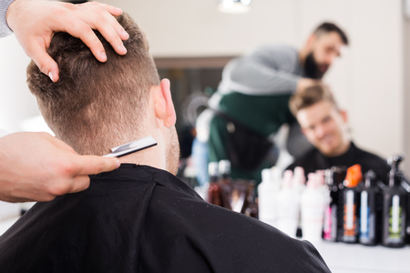haircutter: Positive man hairdresser doing new haircut for guy client at hair salon Stock Photo