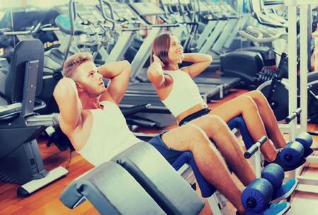 situp: well trained man coach assisting cheerful young woman to make abs exercise sit ups in gym indoors . Focus on man Stock Photo