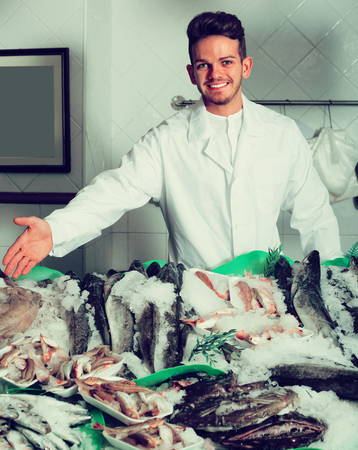 portrait of salesman with apron offering fresh fish in shop