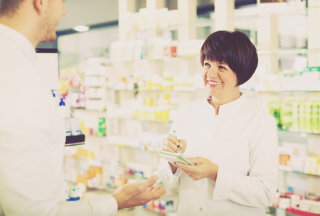 Cheerful woman druggist wearing white coat giving advice to customer in pharmacy Stock Photo