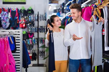sleeveless hoodie: Smiling happy positive couple examining various sports clothes in sports store Stock Photo