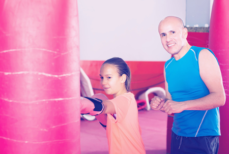 Boxer girl shows her skills to the coach in boxing training Stock Photo