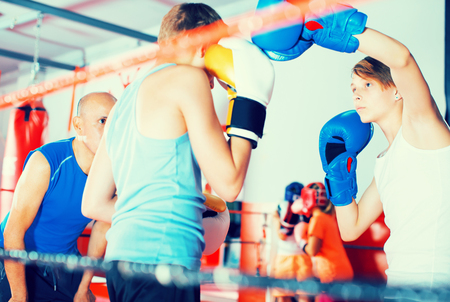 Group of kids exercising with mentor on boxing ring at gym
