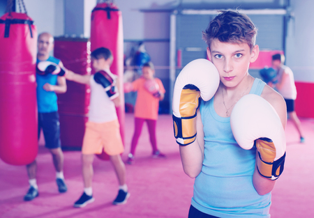 Portrait of young diligent  boy boxer wearing gloves at boxing hall