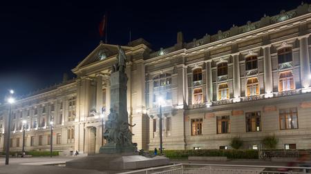 Vista del Palacio de La Moneda en la noche con luces de la ciudad en Santiago Editorial