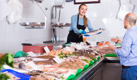 Positive young female seller offering fresh fish and chilled seafood to client