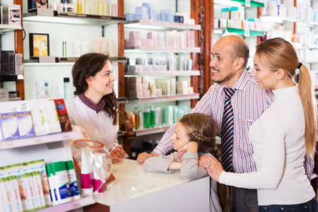 paying: Positive parents with a small girl standing next to cashier and consulting a pharmacist in drugstore. Focus on woman Stock Photo