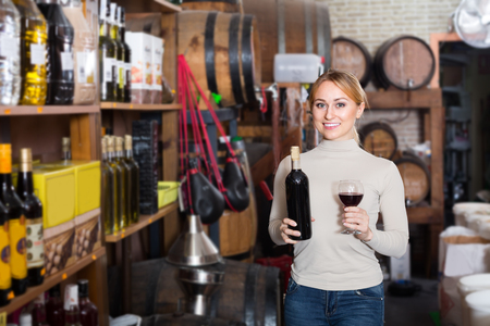 27 years old: cheerful woman 20-27 years old holding bottle of wine in wine house