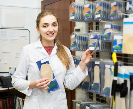 Young russian professional physician offering orthopaedic insoles in special shop