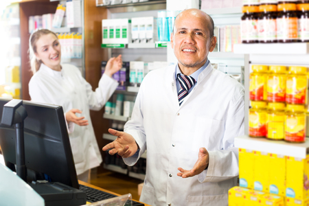 Cheerful elderly pharmacist and female young assistant working at farmacy reception