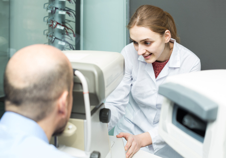 advise: Friendly russian female ophthalmologist and mature patient checking eyesight in clinic