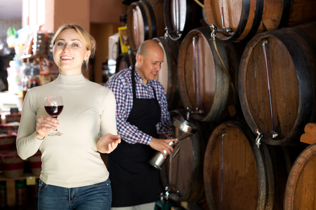 white wine: Positive woman having  glass of wine and standing next to woods in winery Stock Photo
