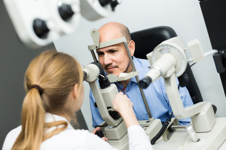 Friendly female ophthalmologist and american mature patient checking eyesight in clinic