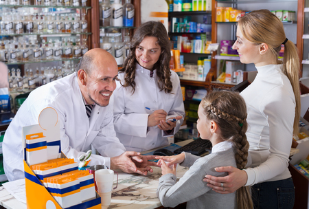 paying: Young mother with a girl consulting two pharmacists at the cash desk at a pharmaceutical store