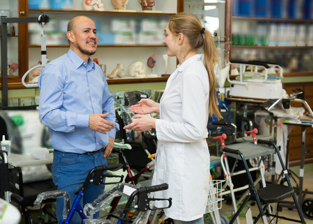 Happy man asking doctor about wheelchairs in store Stock Photo
