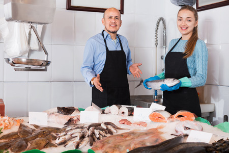 Ordinary fish and seafood store with two smiling satisfied friendly sellers indoors Stock Photo